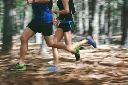 Couple running fast through the forest on trail run with motion blur photo