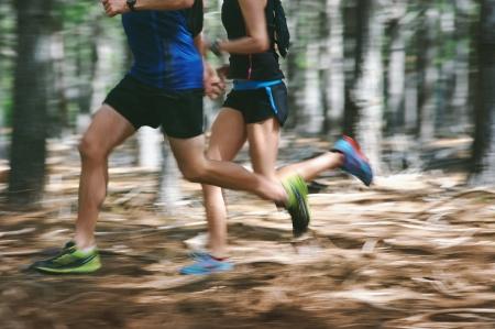 Pareja corriendo rápido a través del bosque en la ejecución del rastro con el desenfoque de movimiento