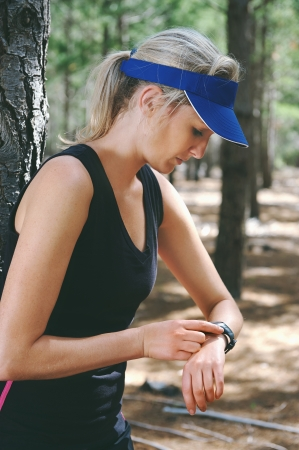 pace: Woman runner checking pace on gps sports watch in forest Stock Photo