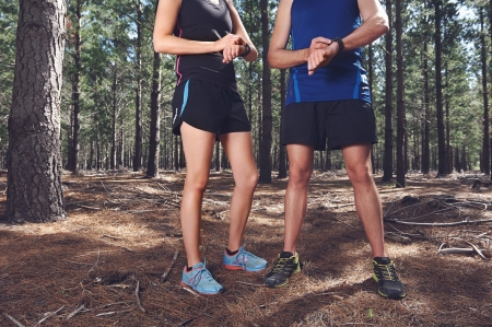 Trail running couple check time on their gps watch for tracking pace photo