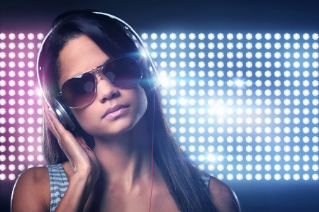 females: Portrait of woman dj enjoying music on headphones and nightclub lights