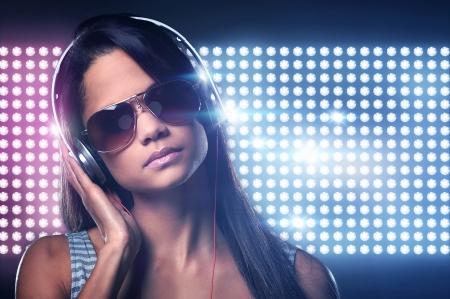 auriculares dj: Retrato de DJ de la mujer disfrutar de la música en los auriculares y luces de discoteca