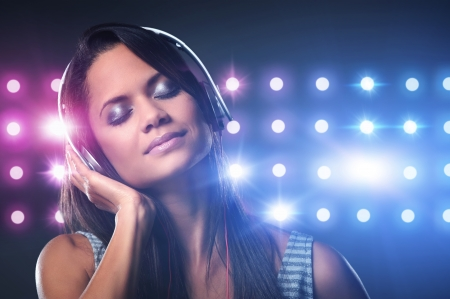 Portrait of woman dj enjoying music on headphones and nightclub lights photo