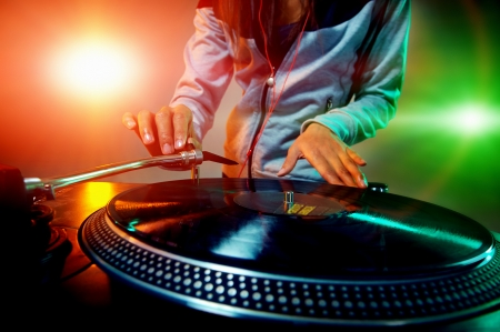 audio mixer: Dj hands on equipment deck and mixer with vinyl record at party