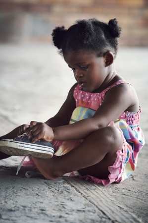젊은 아프리카 여자가 신발 끈을 묶는 및 농촌 환경에 발에 촬영을 가하고