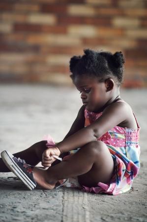 black tie: Joven muchacha africana que ata el cord�n y poner rodaje a pie en un entorno rural