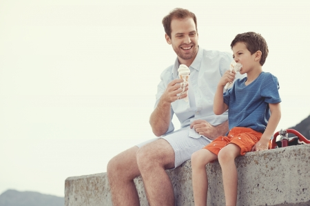 cream: Father and son eating icecream together at the beach on vacation having fun with melting mess