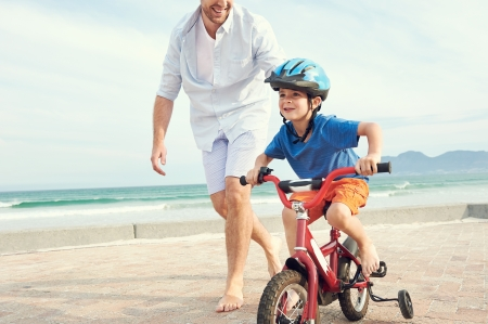 Father and son learning to ride a bicycle at the beach having fun together photo