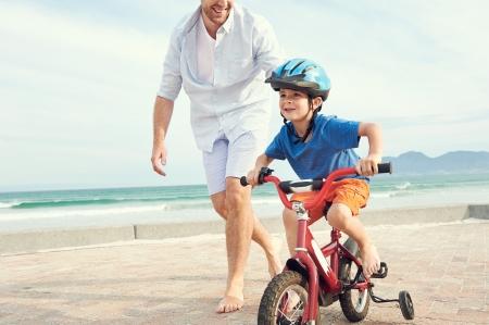 Otec a syn se učí jezdit na kole na pláži spolu baví Reklamní fotografie