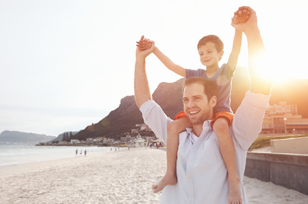 two parents: Son on fathers shoulders at the beach having fun at sunset together Stock Photo