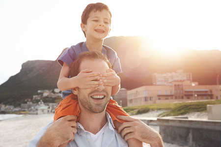 Son on fathers shoulders at the beach having fun at sunset together Stock Photo