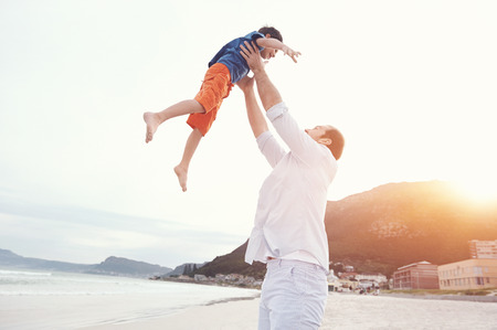 Father throwing son in air at beach having fun playful laughing dad
