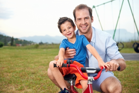 portrait of dad teaching son how to ride his new bicycle in the park, happy smiling family