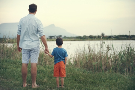 아버지와 아들이 손을 잡고 일몰 산에서 호수 위에 밖으로 찾고