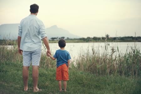 looking at view: Padre e figlio si tengono per mano affaccia sul lago alla montagna al tramonto Archivio Fotografico