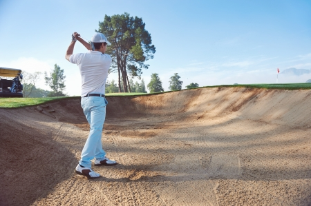 Golfer playing bunker shot photo