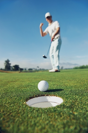 putting green: Golf man putting on green for birdie while on vacation Stock Photo