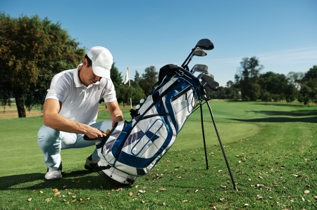 Golfer getting ball from bag on course