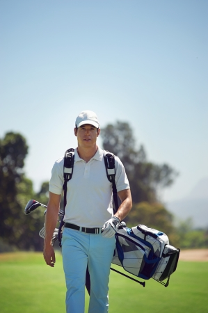 Golf man walking with shoulder bag on course in fairway photo