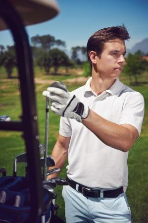 golf man choosing correct iron club to play next shot photo