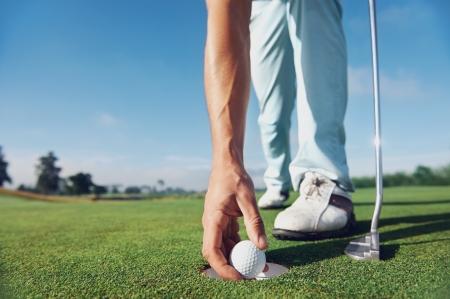 休暇中にバーディーのグリーンを置くゴルフ男