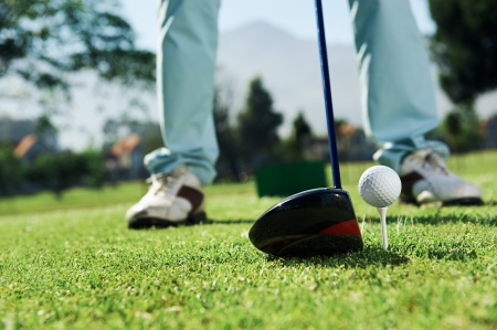 Golfer hitting driver club on course for tee shot Stock Photo