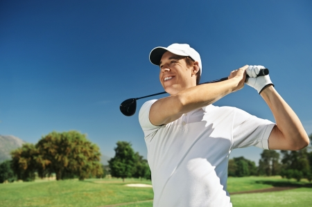 Golfer hitting driver club on course for tee shot Stok Fotoğraf