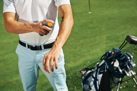 sunblock: Golf sport man with sunblock lotion spray for spf protection