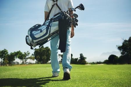 페어웨이에있는 과정에 어깨에 매는 가방과 함께 산책하는 골프 남자