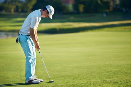 Golf man putting on green for birdie while on vacation Banco de Imagens