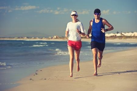 pár běhu naboso na pláži při západu slunce na zdravý životní styl Reklamní fotografie