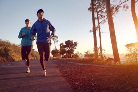 Běh při východu slunce pár cvičení na maratonu a cvičení fitness Reklamní fotografie