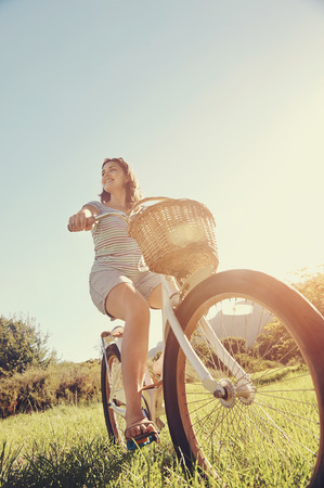 Carefree woman riding bicycle in park having fun on summer afternoon photo