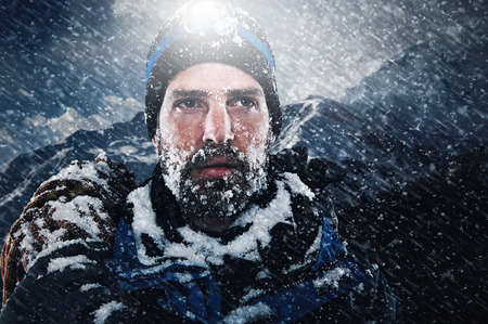 adventure sports: adventure mountain man in snow blizzard looking on with determination and courage