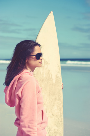 Hispanic woman standing with surfboard at beach looking at waves in the ocean photo