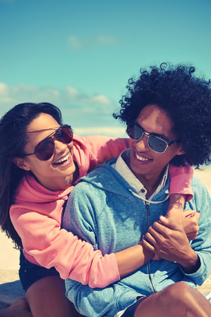 Fun Latino couple at the beach embracing and in love smiling photo