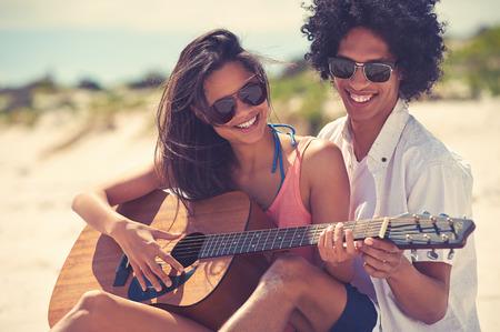 jugando: Linda pareja hispana, tocar la guitarra serenatas en la playa en el amor y abrazar