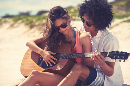 Cute hispanic couple playing guitar serenading on beach in love and embrace photo