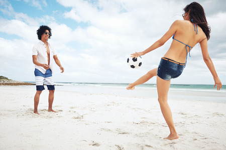 Latino couple playing soccer on beach with ball kicking and having fun photo
