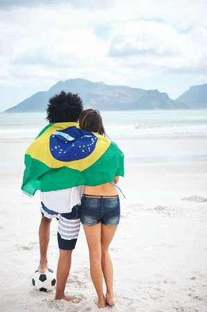 Brazil soccer fans stand on beach together with flag for world cup with ball photo