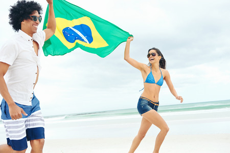 Latino hispanic couple are Brasil fans and hold flag having fun together photo