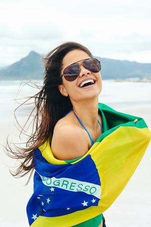Latino žena s Brasil vlajkou smát a usmíval se na podporu brazilské fotbalový fanoušek Reklamní fotografie