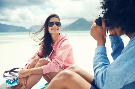 Couple having fun taking photos with retro vintage hipster camera at beach
