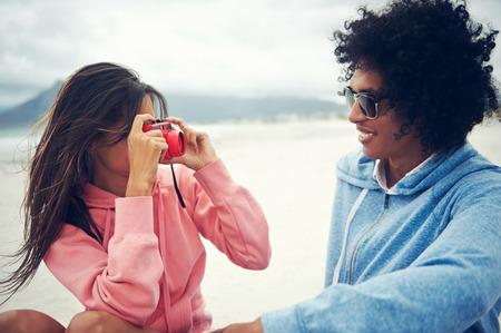 Couple having fun taking photos with retro vintage hipster camera at beach photo