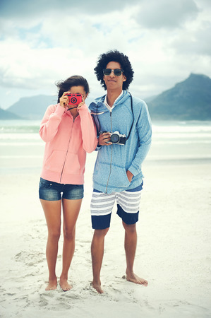 Fashionable hipster couple taking retro camera photo at beach photo