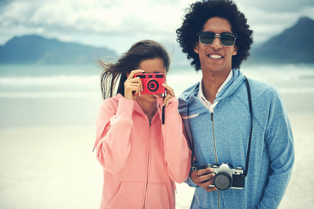 Couple having fun taking photos with retro vintage hipster camera at beach photo