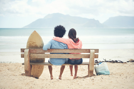 Couple sitting on bench together at the beach in love photo