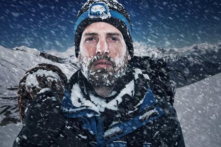 Adventure hombre de la montaña en la expedición de la nieve con material de escalada y determinación Foto de archivo