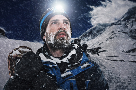 expedition: Adventure mountain man in snow expedition with climbing gear and determination