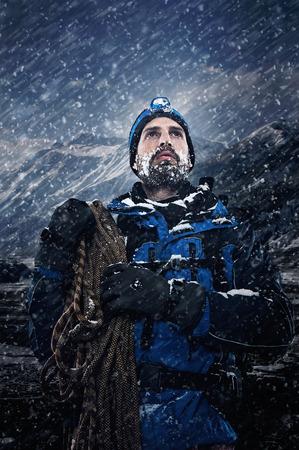 Adventure mountain muž v sněhu expedice s horolezecké vybavení a odhodlání